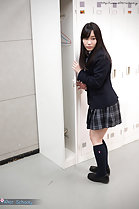 Student opening locker wearing uniform