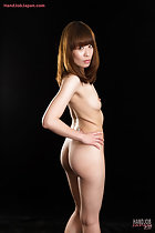 Standing nude hand on hip looking over her shoulder long hair small breasts bare ass