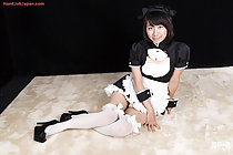 Seated in maid uniform wearing apron in stockings and heels