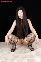 Squatting in high heels long hair down over her lingerie in fishnet stockings legs open exposing her pussy