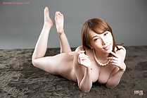 Lying on her front naked bare feet raised wearing pearl necklace