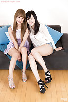 Girls seated together on sofa long hair wearing high heels