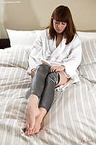 Sitting on bed long hair down to her white robe pulling on skin tight silver pants bare feet