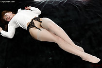 Lying on her back wearing white blouse in stockings and garter belt