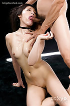 Shiina Mizuho seated nude on her side head tilted to the side cock in her mouth hand on her small breasts shaved pussy