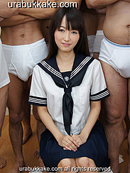 Misa Sitting In Front Of Half Naked Men Wearing Uniform Hands Clasped On Her Lap