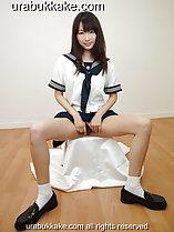 Kogal seated in uniform long hair to her shoulders sitting with her legs spread hands between her legs