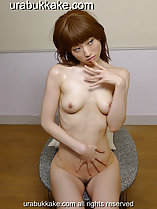 Seated on bench fingers to her lips small breasts