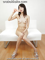 Misa sitting naked on couch dildo raised to her lips long hair small tits knees pressed together wearing high heels